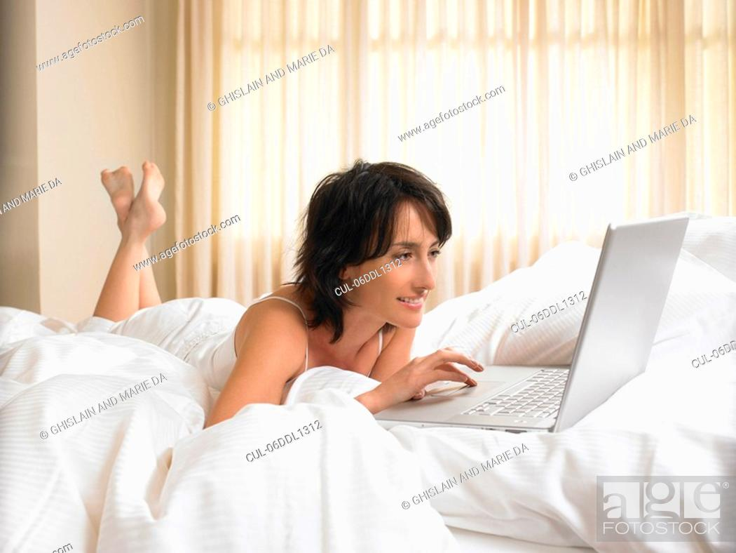 Stock Photo: Woman in bed with computer.