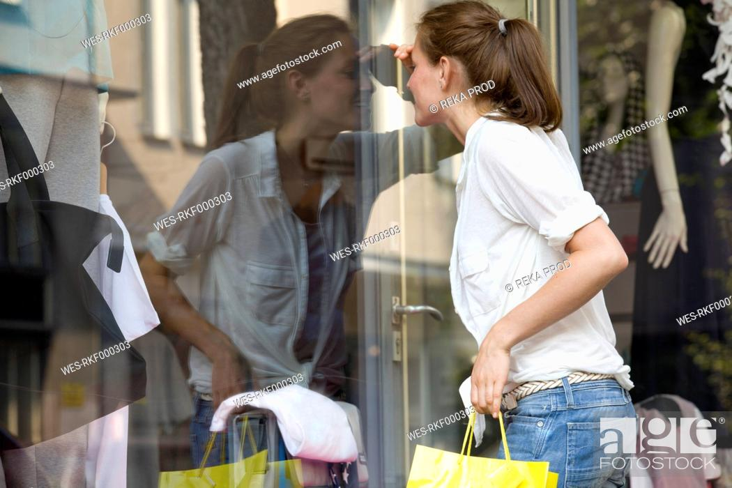Stock Photo: Germany, North Rhine Westphalia, Cologne, Young woman at window shopping.