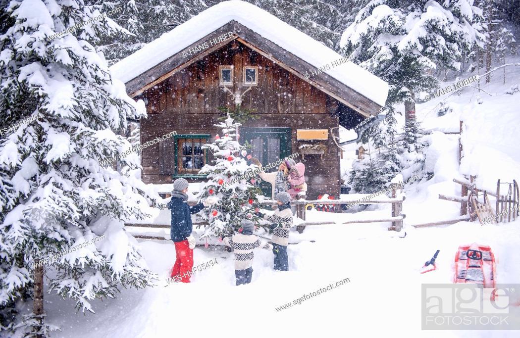 Stock Photo: Austria, Altenmarkt-Zauchensee, family decorating Christmas tree at wooden house.