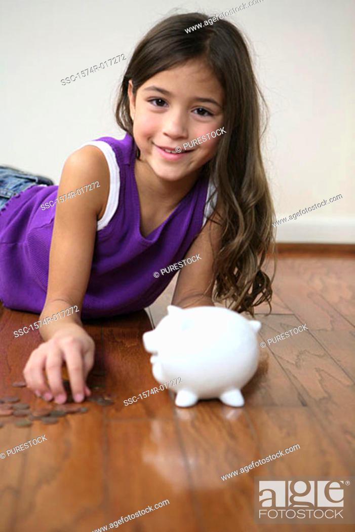 Stock Photo: Portrait of a girl lying on the floor with a piggy bank in front of her.