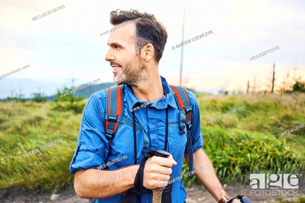 Photo de stock: Smiling man hiking in the mountains turning round.
