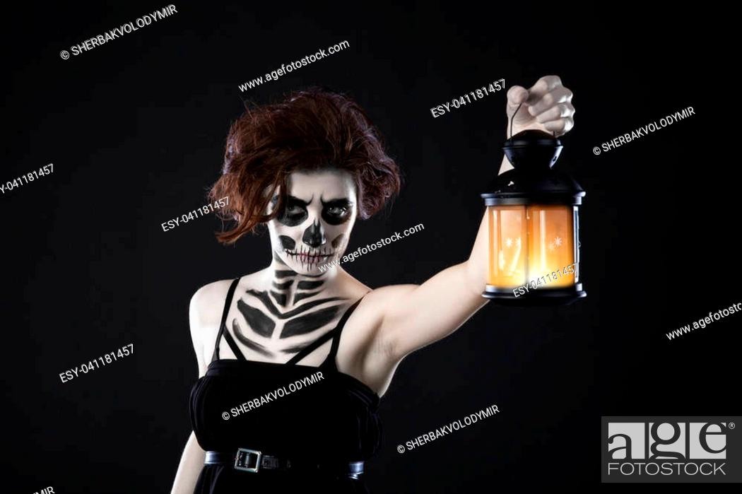 Imagen: Scary woman with lantern in night scene - Spooky image of a scary woman with dark eyes and appearance of a witch, in a white dress, holding a lit lantern.