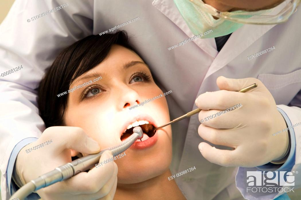 Stock Photo: Image of young woman keeping her mouth open while dentist examining it.