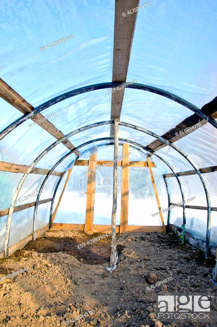 Stock Photo: Homemade plastic arch empty greenhouse in winter, view inside.