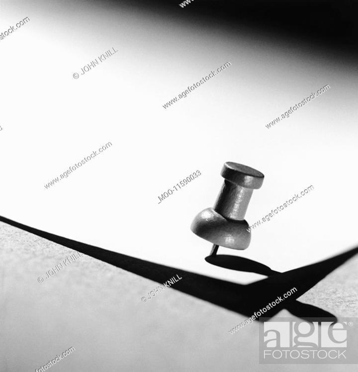 Stock Photo: Push pin holding down paper b&w close-up.