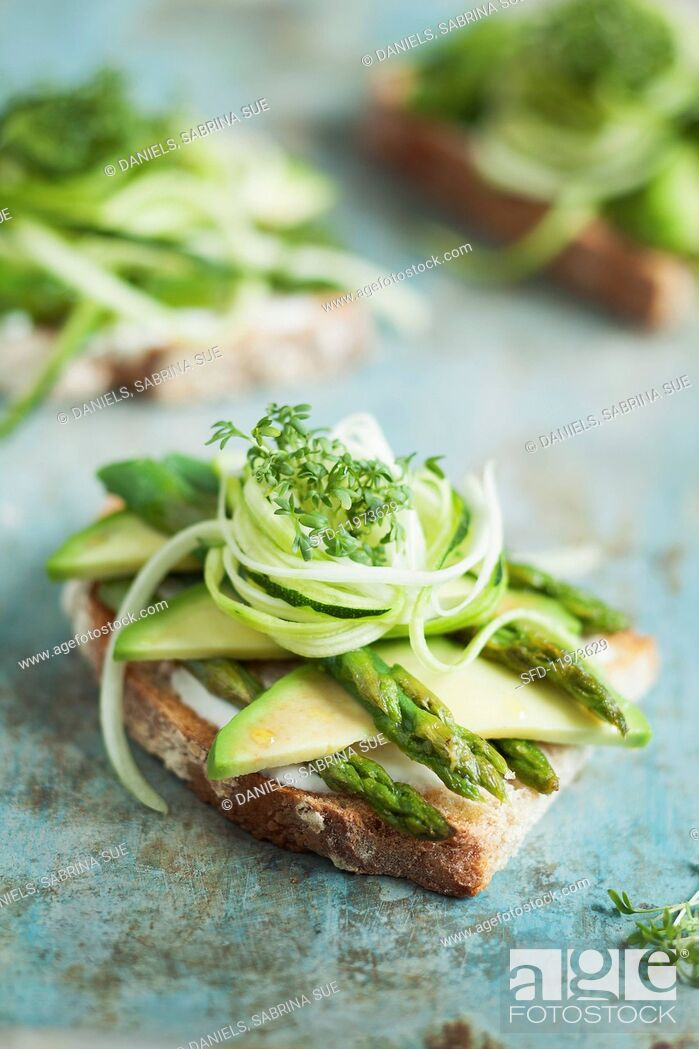 Stock Photo: Grilled bread topped with avocado, green asparagus and cress.