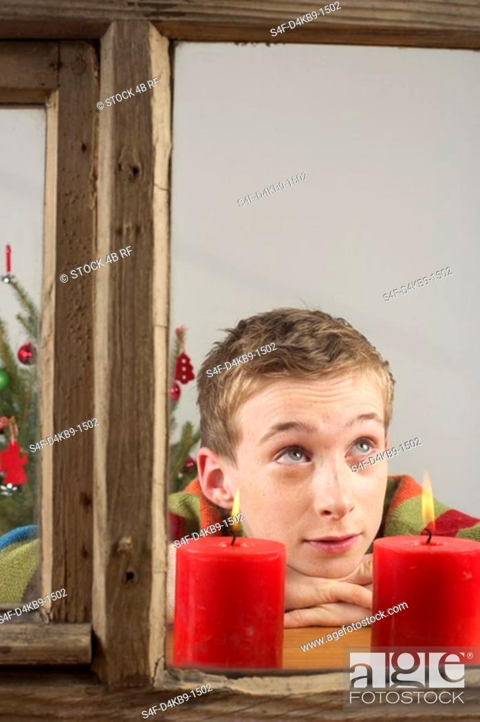 Stock Photo: Wishful boy looking out of a window.