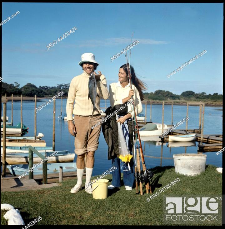 Stock Photo: Christiaan Barnard and his wife Barbara Zoellner fishing. South African surgeon Christiaan Barnard showing a freshly caught fish under the pleased gaze of his.