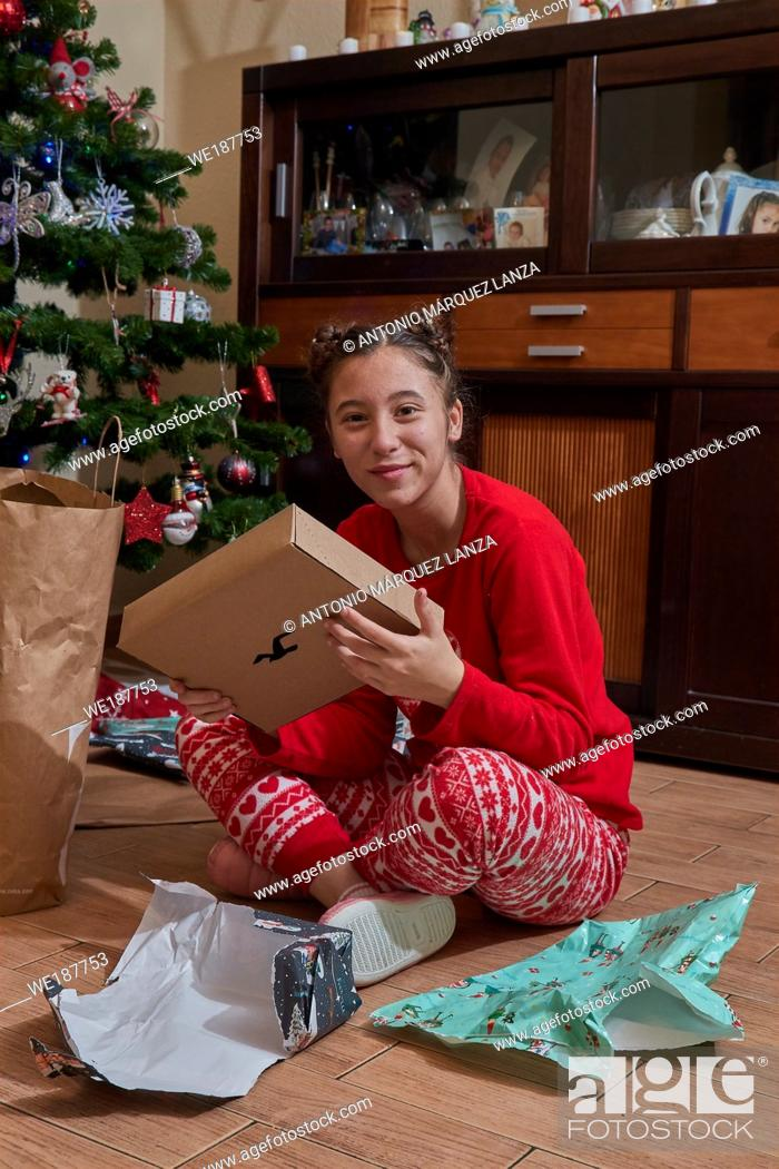 Stock Photo: girl receiving Christmas gifts under the tree.