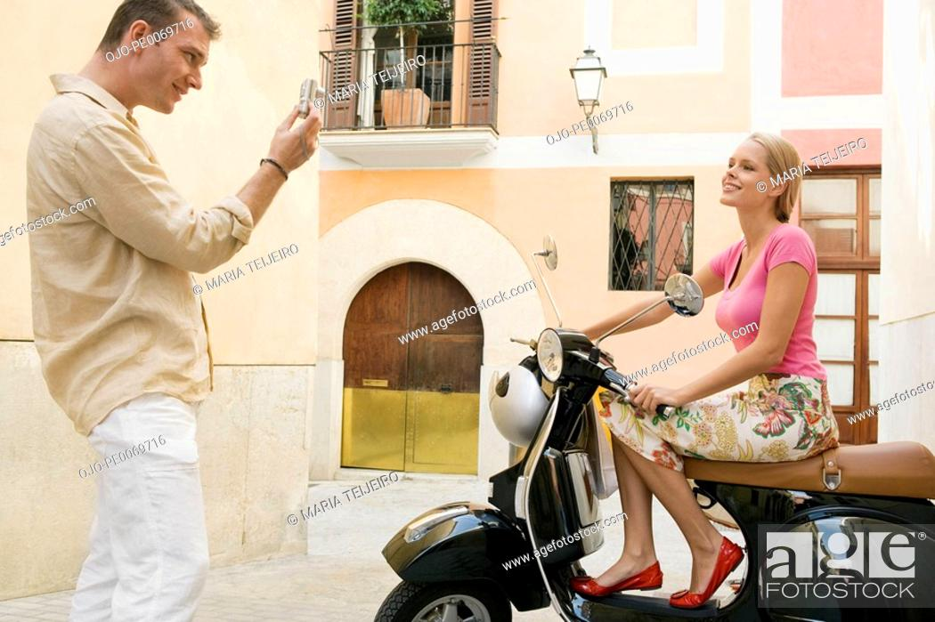 Stock Photo: Man photographing woman on scooter.