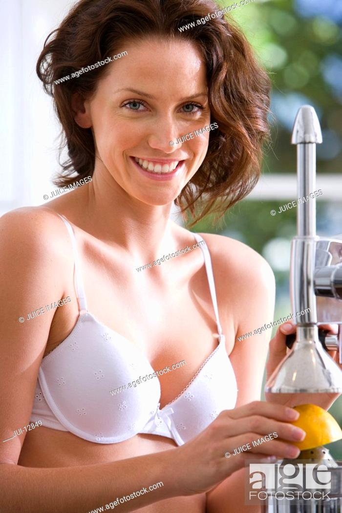 Stock Photo: Young woman in underwear with juicer, smiling, portrait, close-up.