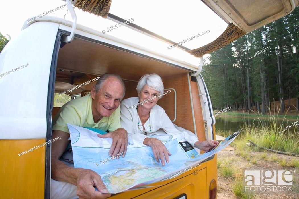 Stock Photo: Senior couple lying in back of camper van reading map, smiling, portrait, low angle view.