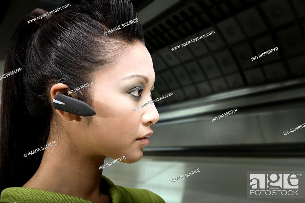 Stock Photo: A woman wearing a bluetooth headset.