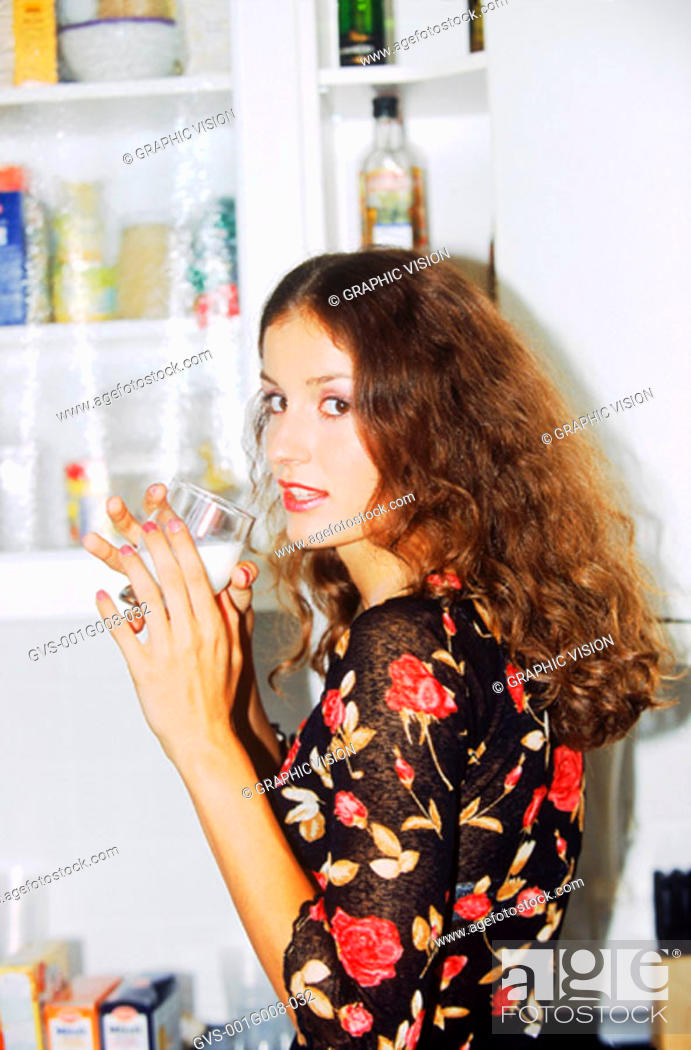Stock Photo: Young woman in a kitchen drinking milk.