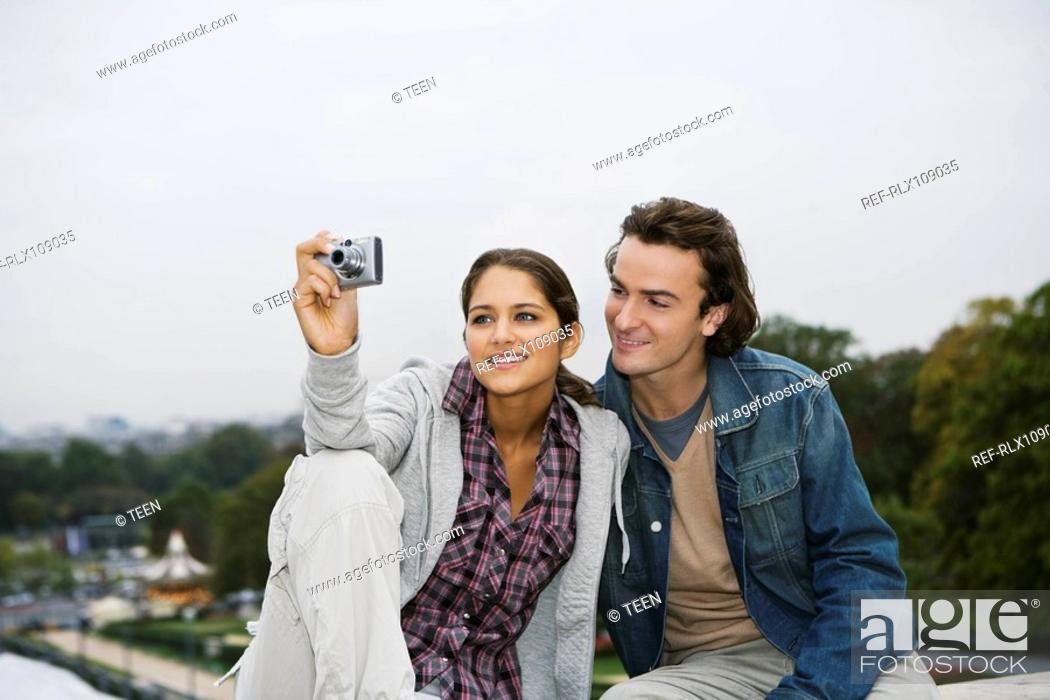 Stock Photo: Young couple sitting on wall, woman taking photo, Paris, France.
