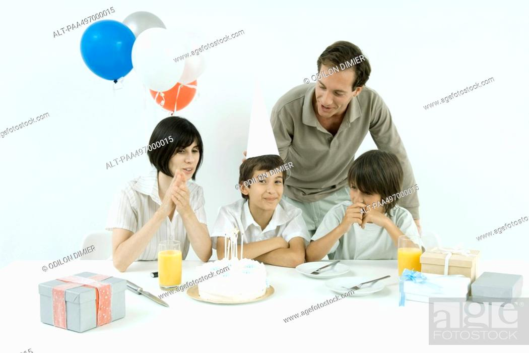 Stock Photo: Boy having birthday party with family, looking at camera.