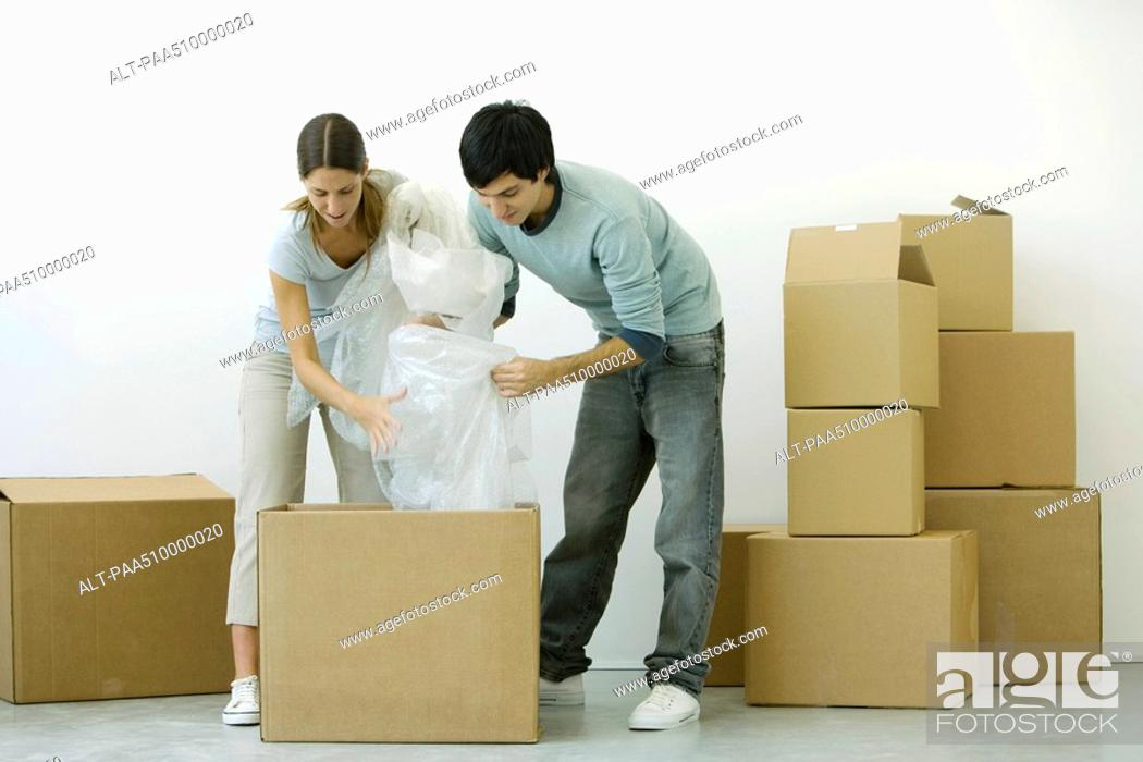 Stock Photo: Couple unpacking cardboard boxes together.