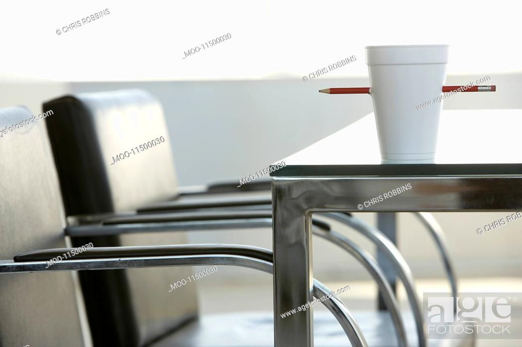 Stock Photo: Cup pierced by pencil on table in office.