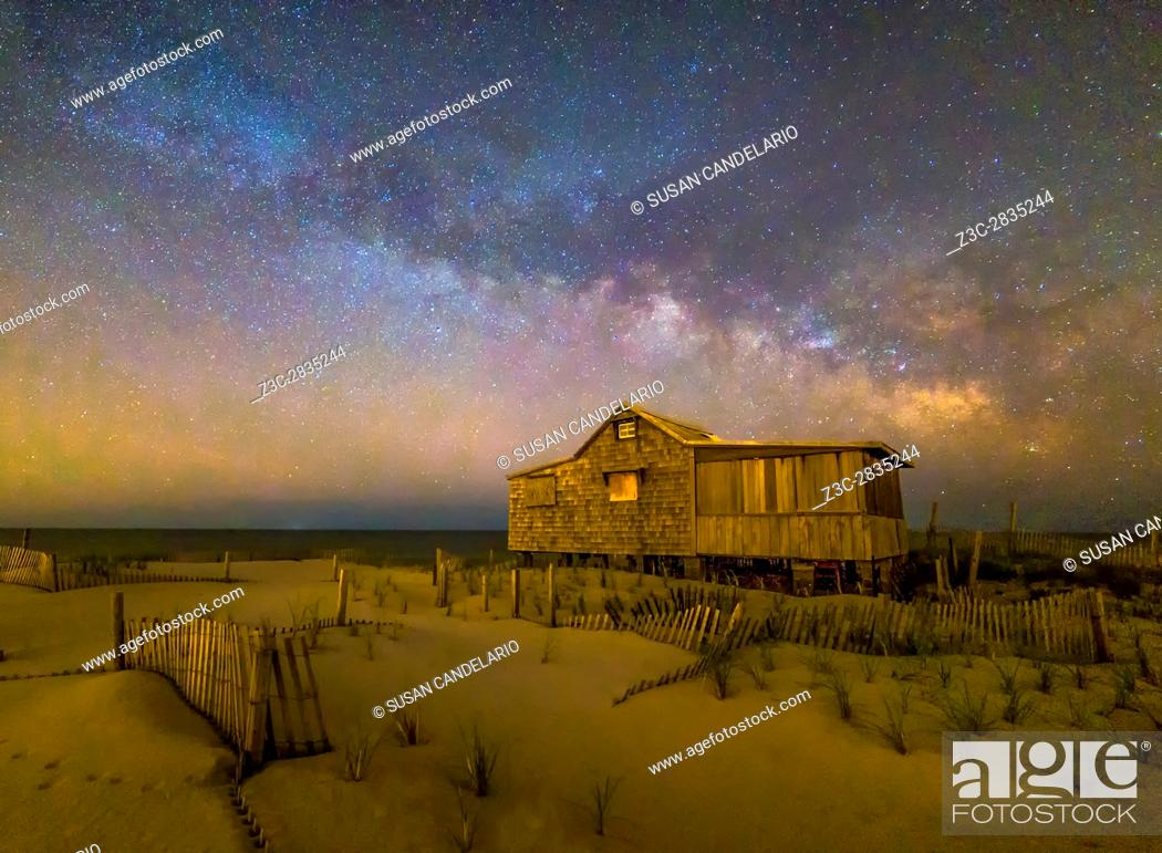 Stock Photo: New Jersey Shore Starry Skies and Milky Way - Island Beach State Park at the NJ Shore with beach fences leading to the Judge's Shack underneath a starry sky.