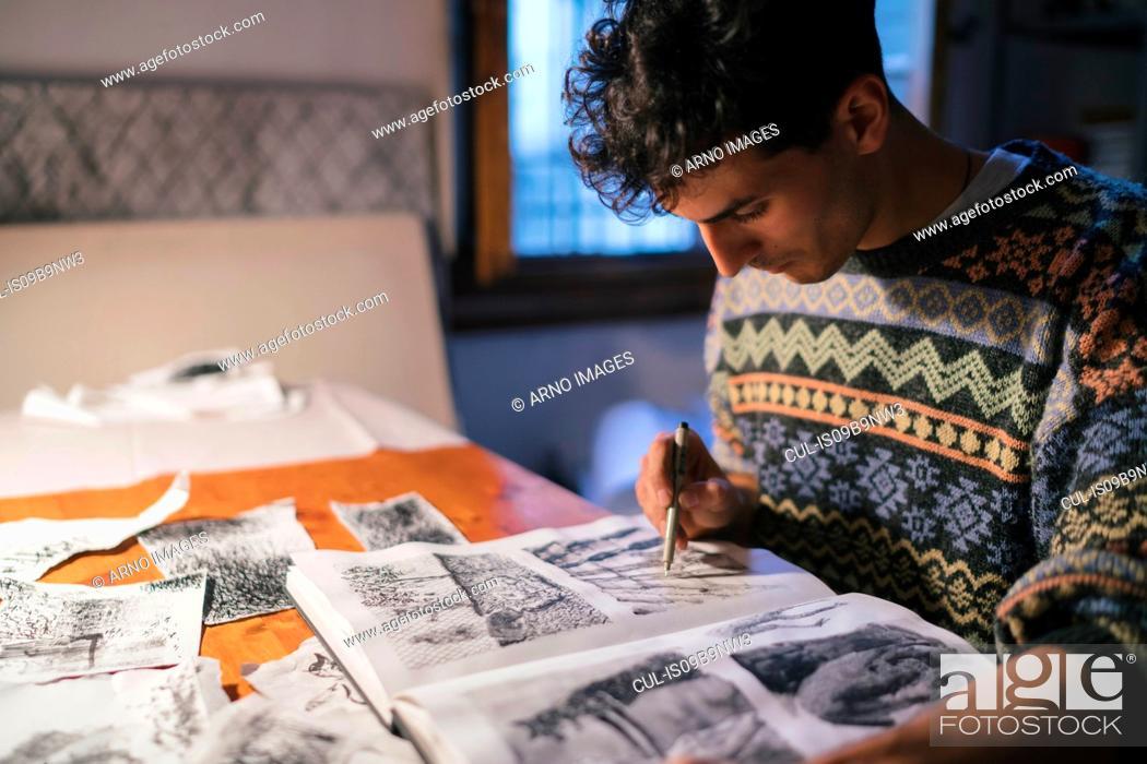 Photo de stock: Male artist drawing in sketchbook at desk in artists studio.
