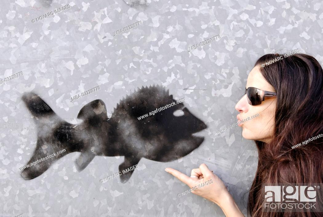 Stock Photo: Woman kisses black graffiti fish on a gray wall,.