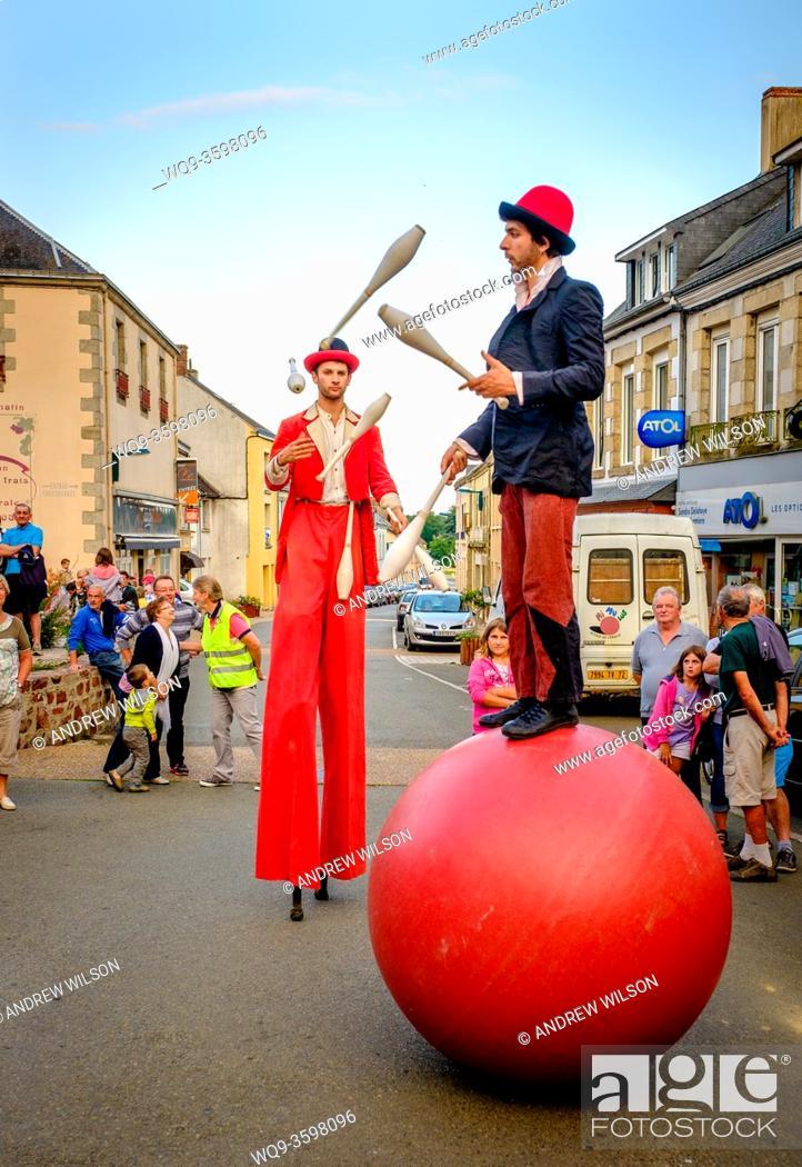 Stock Photo: Jugglers entertain a small crowd in the town of Villaines-la-Juhel, Pays de la Loire, France during bastille Day celebrations.