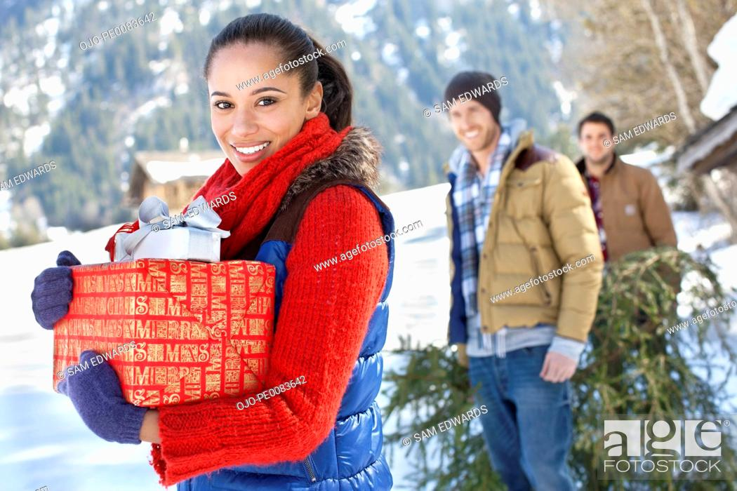 Stock Photo: Portrait of friends with fresh cut Christmas tree and gifts in snow.