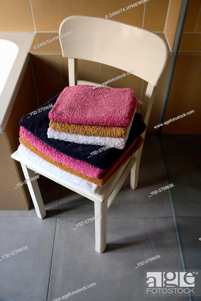 Stock Photo: Interior scene, bathroom, stack of folded towels on vintage white chair near bathtub and shower glass.