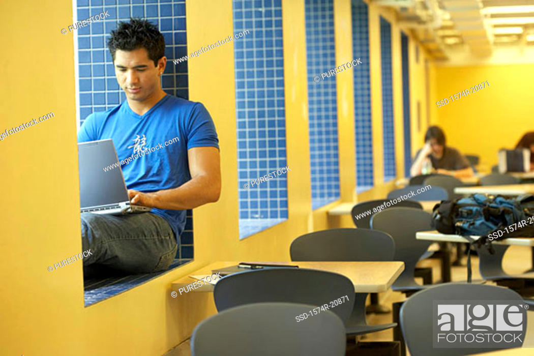 Stock Photo: College student sitting on a window ledge and using a laptop.