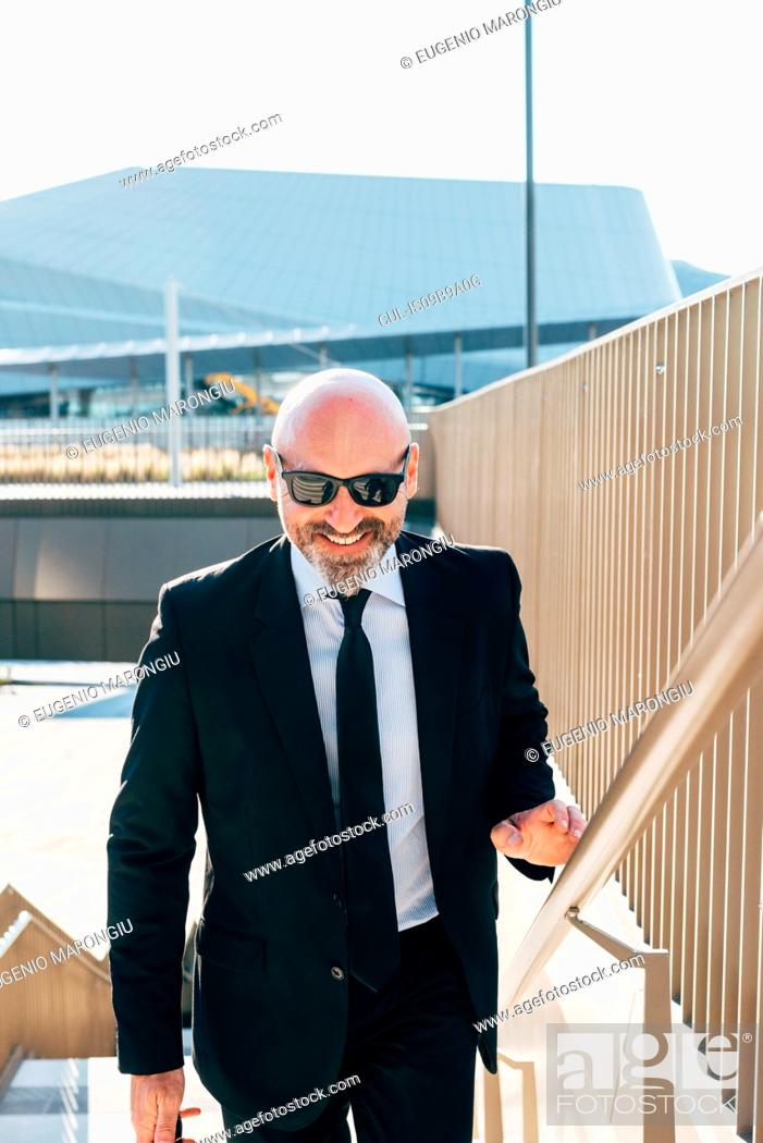 Stock Photo: Portrait of mature businessman outdoors, walking up steps, wearing sunglasses.