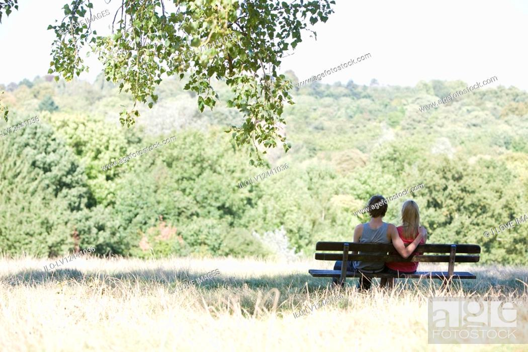 Stock Photo: A young couple sitting on a bench in a park.