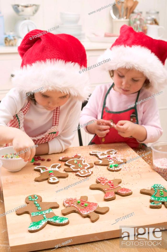 Stock Photo: Two small girls decorating gingerbread men.