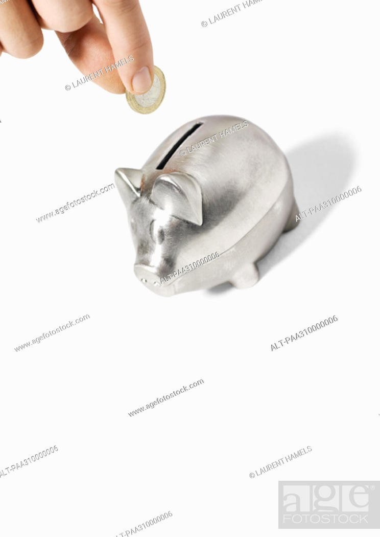 Stock Photo: Hand inserting coin into piggy bank.