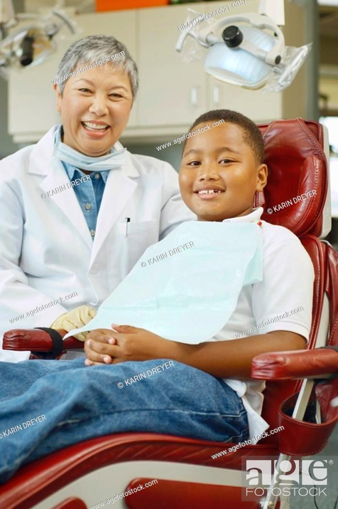 Stock Photo: Senior Asian female dentist and African boy in dentist's chair.
