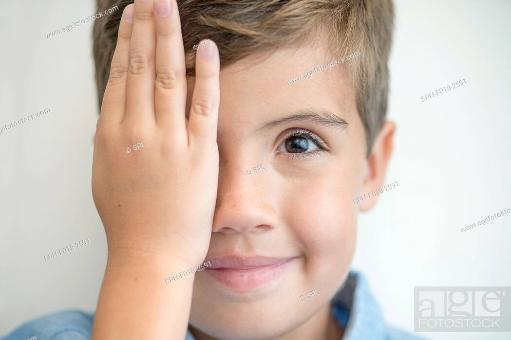 Stock Photo: Boy covering one eye with hand.