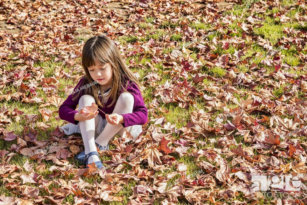 Stock Photo: Five year old girl playing with an autumn leaf.