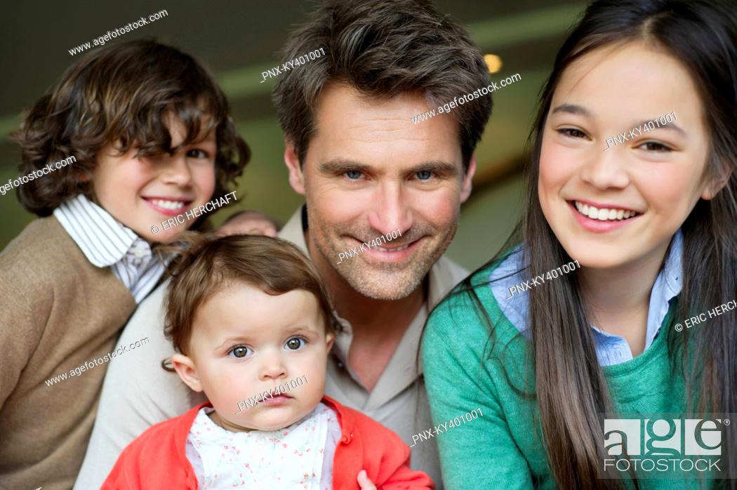 Stock Photo: Portrait of a happy man with their children smiling.