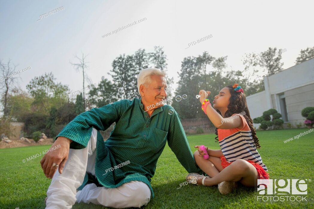 Stock Photo: India, Young girl (6-7) blowing bubbles with grandfather sitting on backyard.