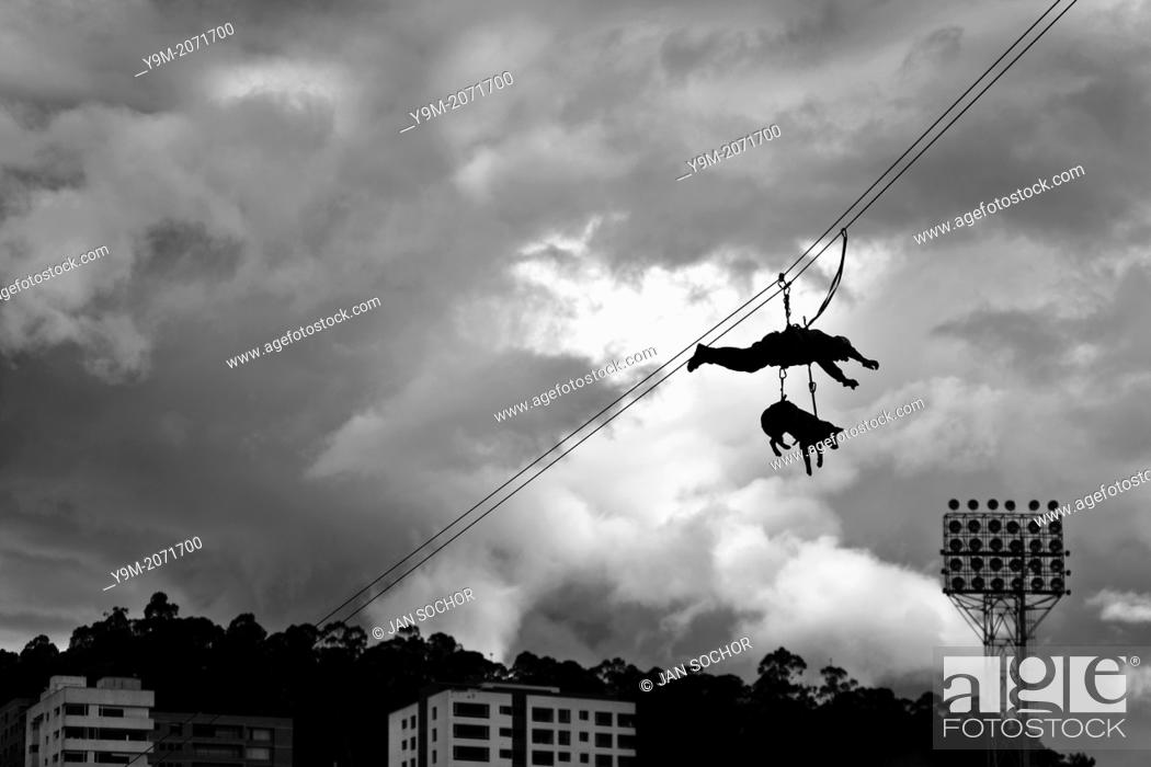 Stock Photo: A member of the Police Rescue team, with his dog attached, rappel down in the air during a public demonstration of the Police forces in Quito, Ecuador.