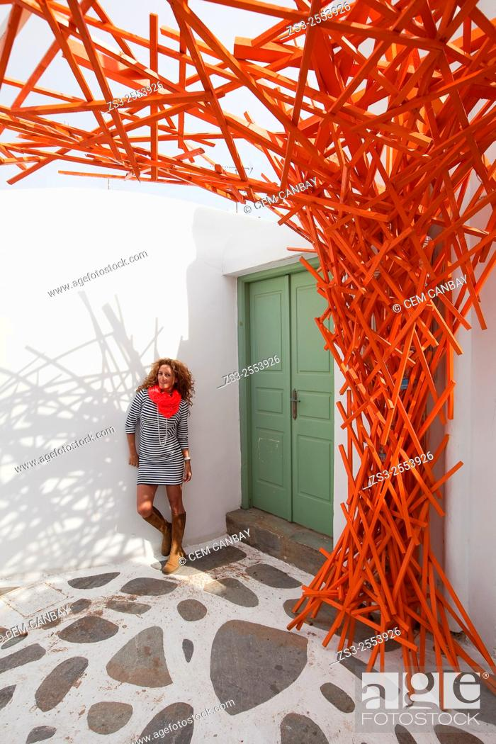 Stock Photo: Woman posing with an orange scarf near a whitewashed house in town center, Mykonos, Cyclades Islands, Greek Islands, Greece, Europe.