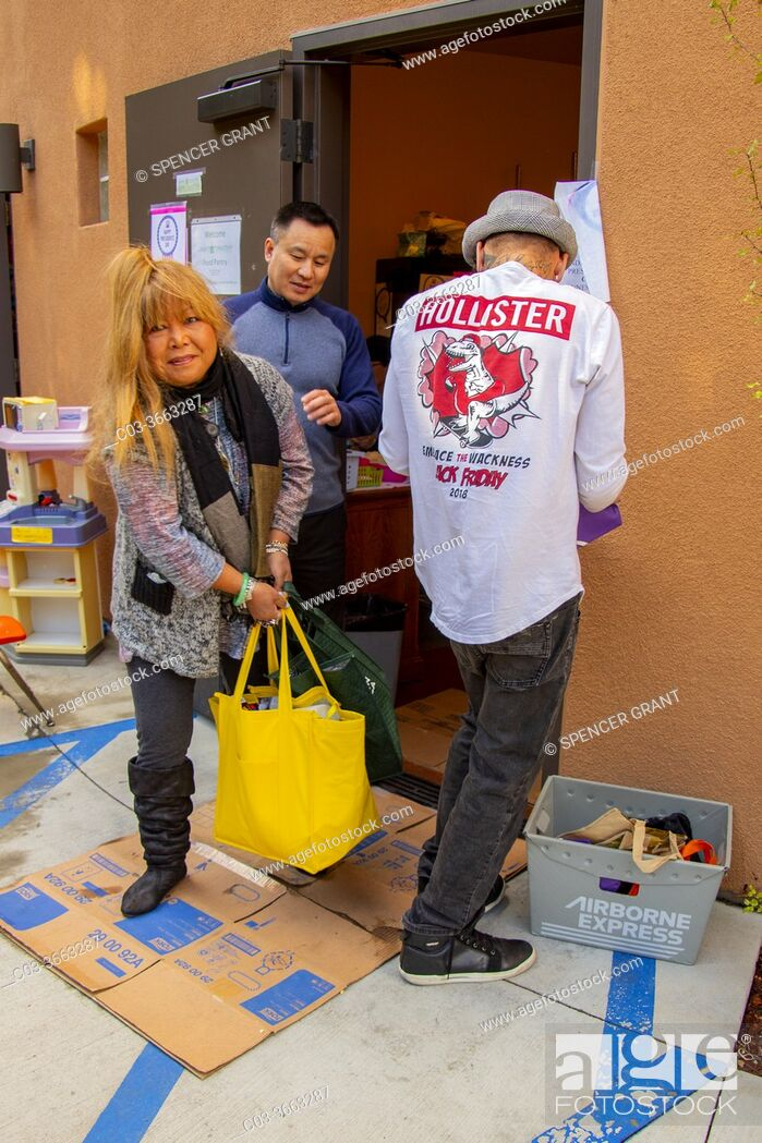 Stock Photo: A Vietnamese American priest officiates as Hispanic and Caucasian charity clients carry food from the free pantry of a Southern California Catholic church.