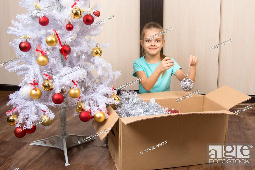 Imagen: Happy little girl puts a shot with Christmas trees Christmas balls in a box.