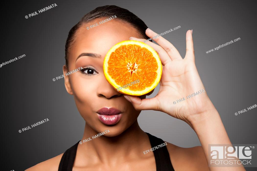 Stock Photo: Beautiful healthy happy black asian woman holding delicious orange mandarin fruit in front of eye.