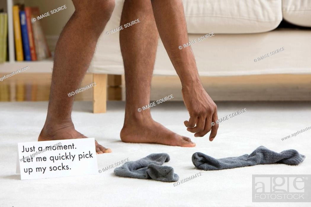 Stock Photo: A man picking up socks.