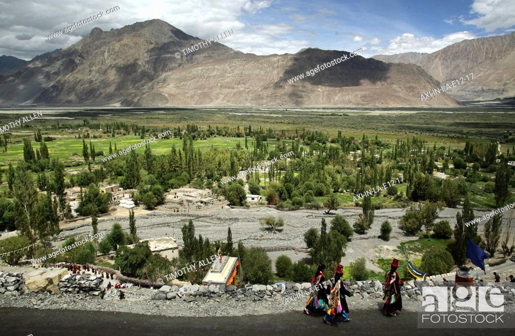 Imagen: Women in traditional dress walking along road at base of mountains.