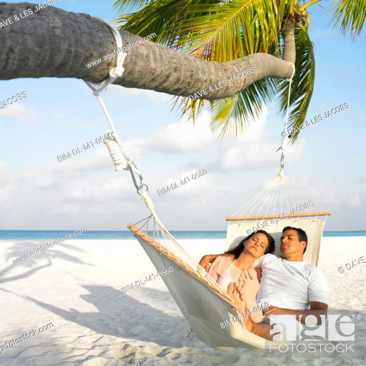 Stock Photo: Couple sleeping in a hammock.
