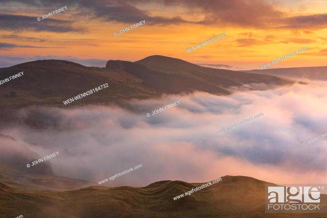 Stock Photo: The view from Little mam Tor looking down Hope Valley with the light from the rising sun catching the swirling fog over the Derbyshire Peak District.