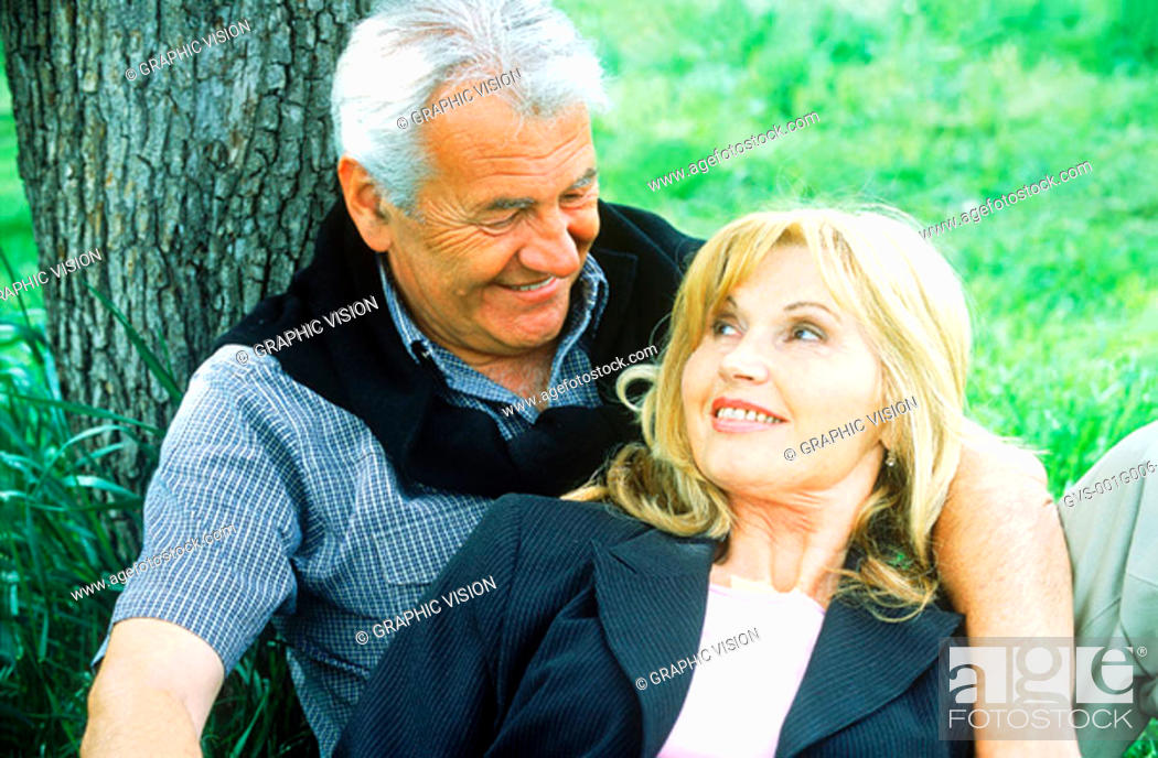 Stock Photo: Mature couple sitting against a tree smiling.