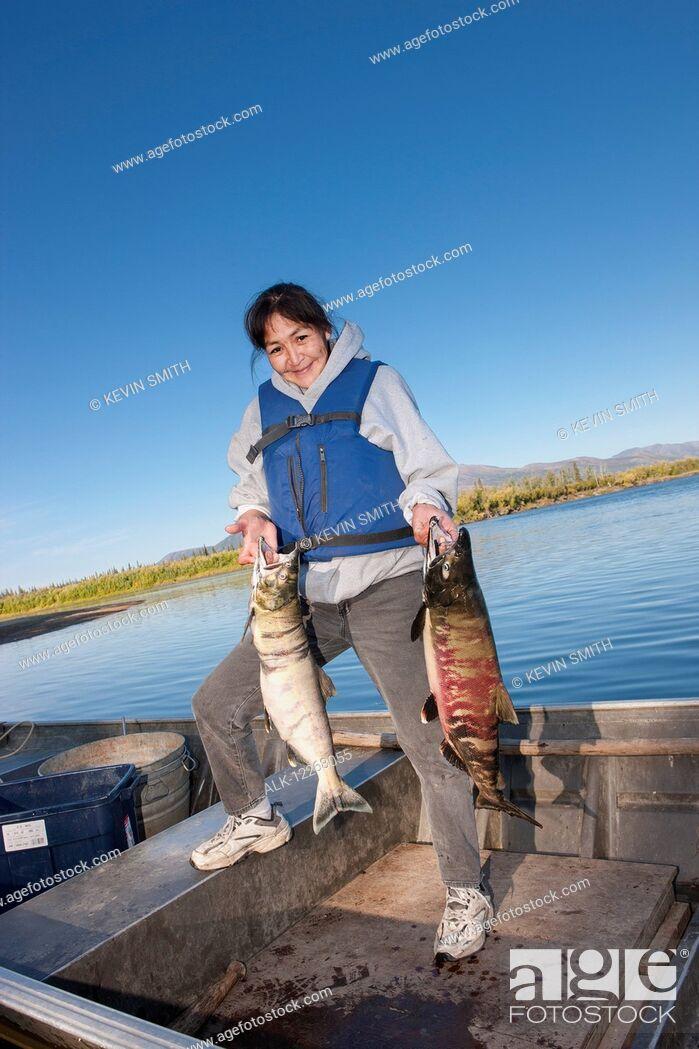Imagen: Alaska native female standing in a motor boat holding chum salmon, Shungnak, Arctic Alaska, summer.