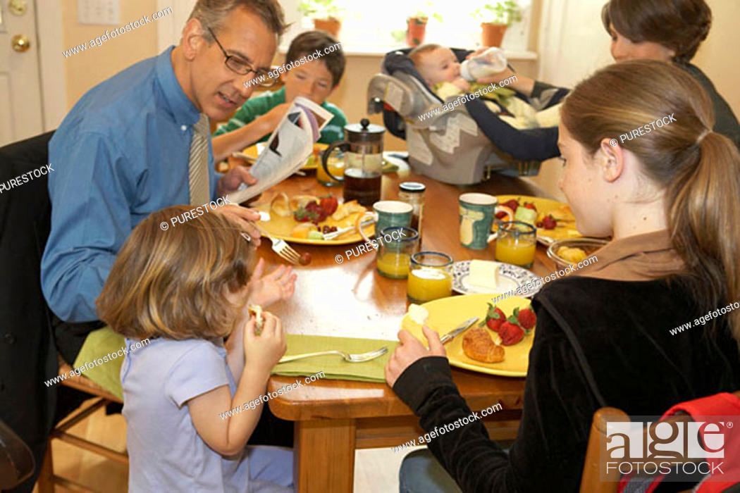 Stock Photo: Mid adult couple having breakfast with their two daughters and two sons.